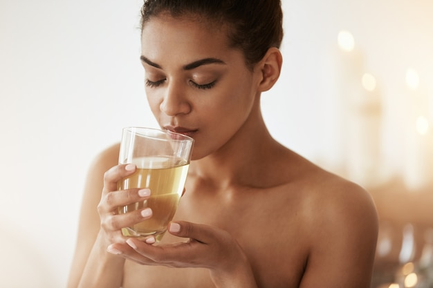 Linda mulher africana bebendo chá sorrindo relaxante no salão spa. Foto gratuita