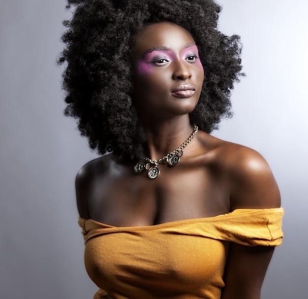 Linda mulher africana com um grande cabelo afro encaracolado e flores no cabelo Foto gratuita