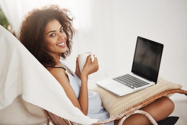Linda mulher africana em roupa de noite sorrindo segurando copo sentado com o laptop na cadeira em casa sozinho Foto gratuita