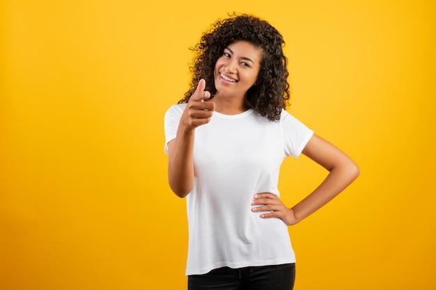 Linda mulher africana negra apontando dedo isolado sobre amarelo Foto Premium