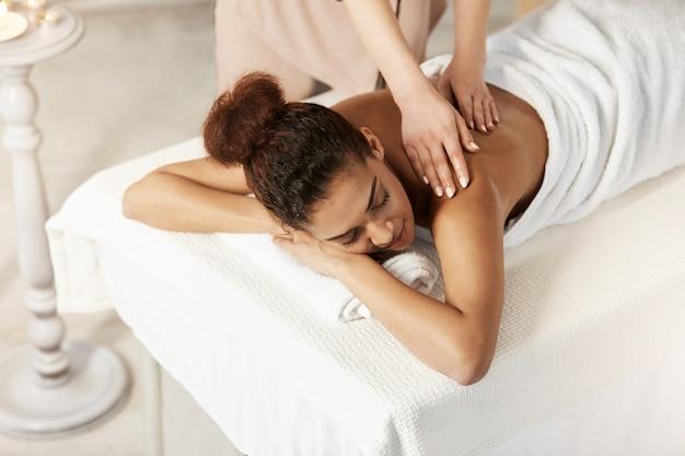 Linda mulher africana sorrindo desfrutando de massagem com os olhos fechados no salão spa. Foto gratuita
