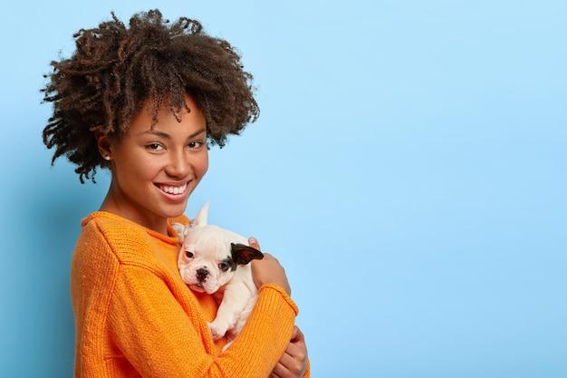 Linda mulher afro-americana fica de lado, brinca com o cachorrinho bulldog em casa, mostra amor entre o dono e o animal de estimação Foto gratuita