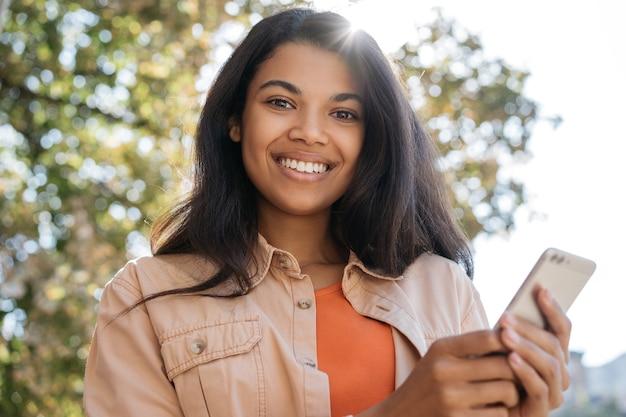Linda mulher afro-americana sorridente, segurando um telefone celular, fazendo compras online, olhando para a câmera Foto Premium