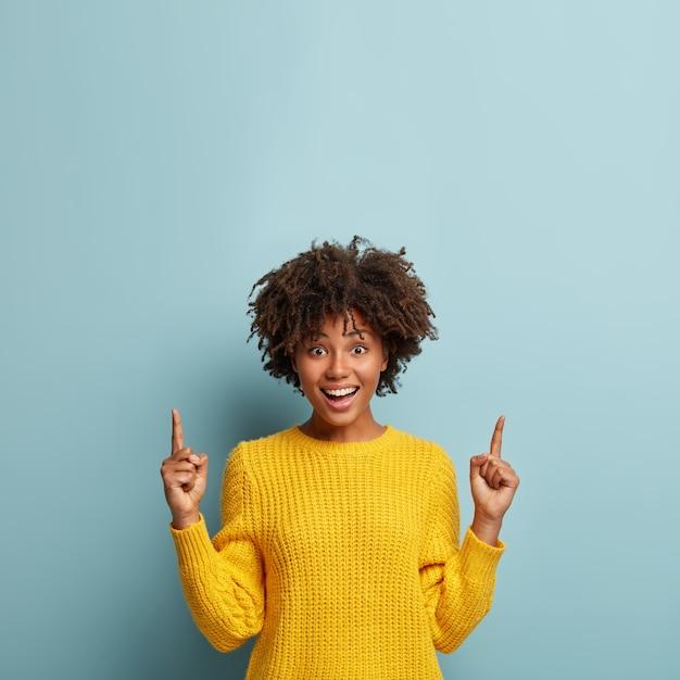 Linda mulher alegre e sorridente com penteado afro, aponta para cima, mostra uma promoção bacana ou uma oferta incrível, vestida com um suéter amarelo, dá conselhos, posa contra um fundo azul Foto gratuita