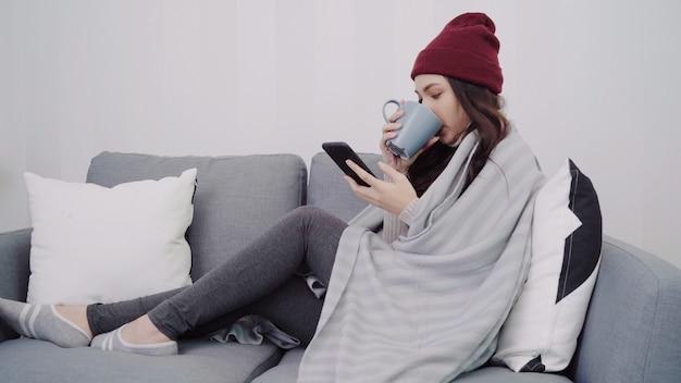 Linda mulher asiática atraente usando smartphone para mensagens de texto e leitura Foto gratuita