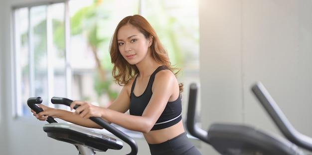 Linda mulher asiática com corpo esbelto, fazendo exercícios cardio na máquina elíptica Foto Premium