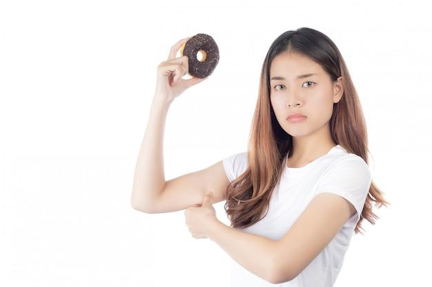 Linda mulher asiática com um sorriso feliz, segurando donut na mão Foto gratuita