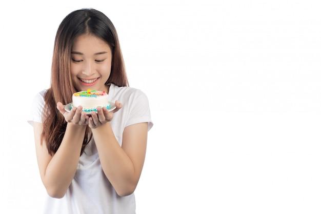 Linda mulher asiática com um sorriso feliz, segurando um bolo na mão Foto gratuita