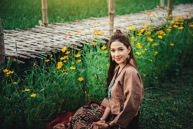 Linda mulher asiática no local vestido sentado no chão e desfrutar natural no campo de arroz Foto Premium