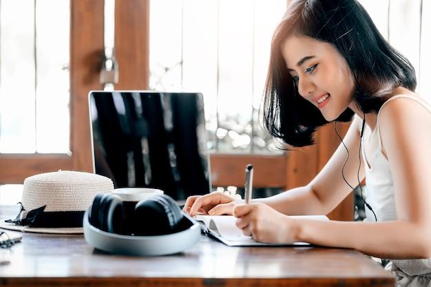 Linda mulher asiática ouvindo música e escrevendo no notebook Foto Premium