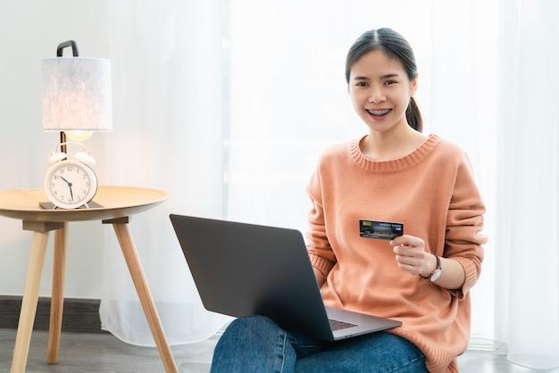 Linda mulher asiática segurando um cartão de crédito e usando laptop digital para fazer compras online Foto Premium