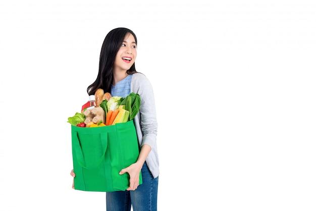 Linda mulher asiática sorridente segurando sacola verde reutilizável cheia de mantimentos e olhando para copiar o espaço de lado isolado no fundo branco Foto Premium