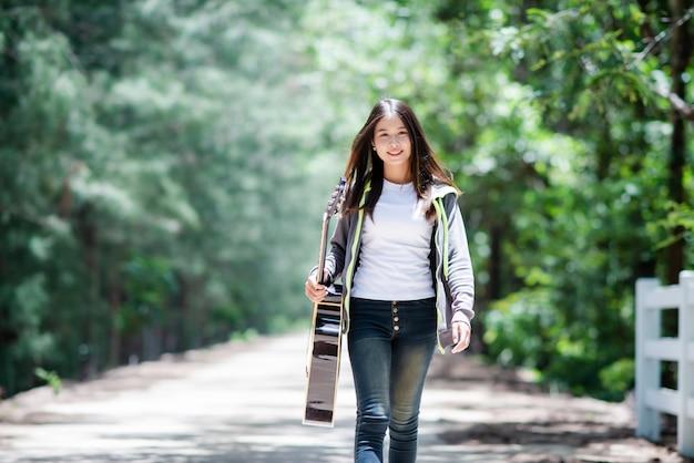 Linda mulher asiática sorrindo com guitarra acústica Foto gratuita