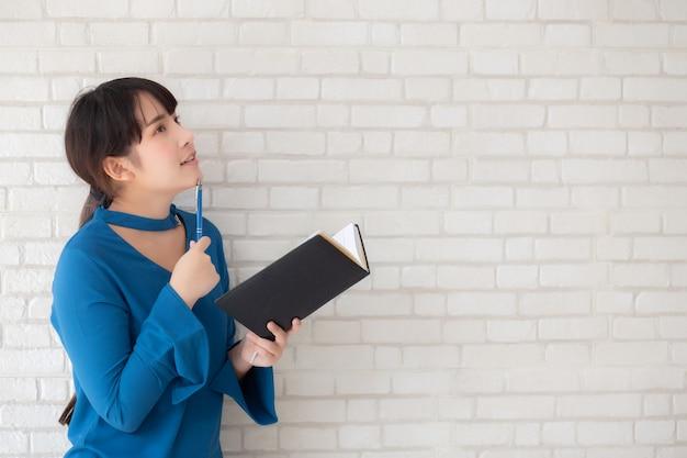 Linda mulher asiática sorrindo em pé pensando e escrevendo o caderno sobre cimento branco fundo de concreto Foto Premium