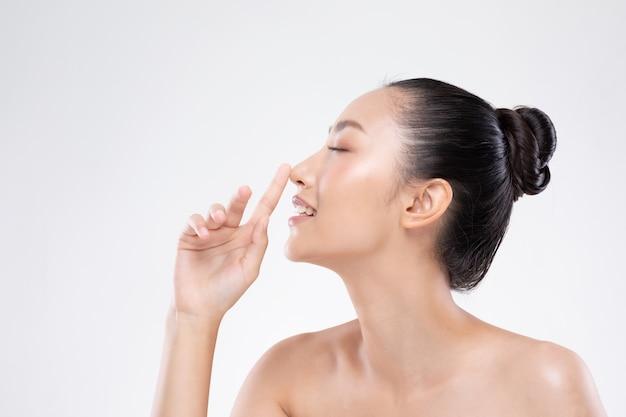 Linda mulher asiática tocando nariz sorrir com pele limpa e fresca felicidade e alegre com emocional positivo Foto Premium