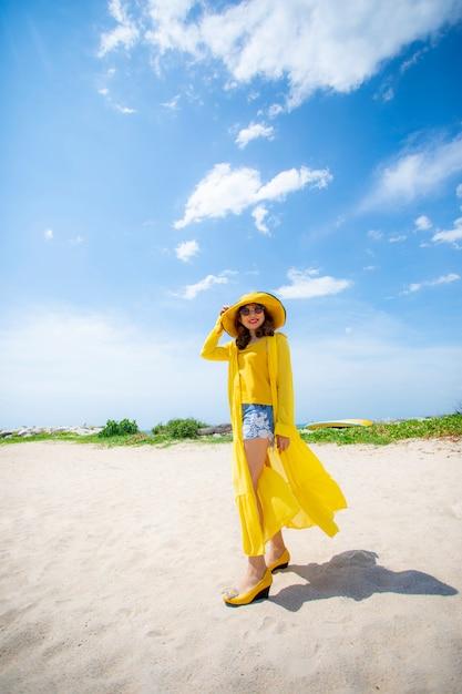 Linda mulher asiática, vestindo roupas amarelas, de pé na praia do mar contra a luz do sol do meio-dia Foto Premium