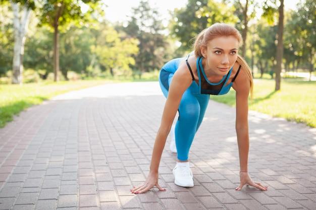Linda mulher atlética malhando no parque de manhã Foto Premium