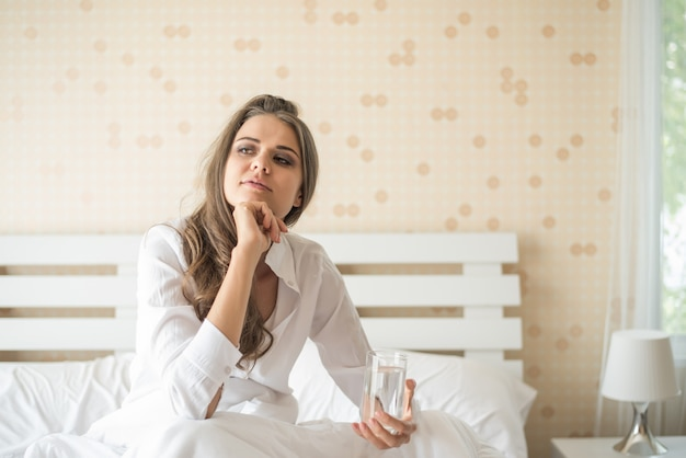 Linda mulher bebendo água fresca na cama de manhã Foto gratuita