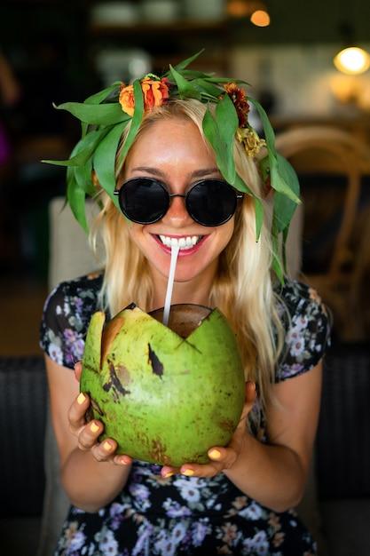 Linda mulher beber coco no café tropical Foto Premium