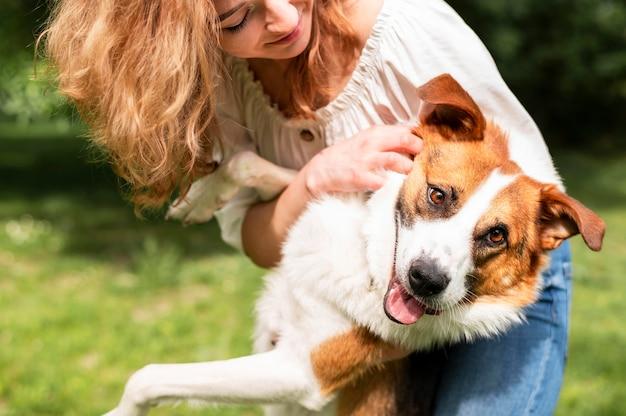 Linda mulher brincando com seu cachorro no parque Foto Premium