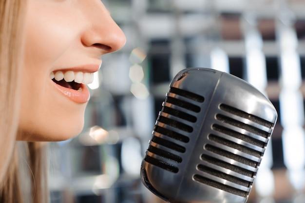 Linda mulher cantando no palco ao lado do microfone. Foto Premium