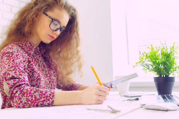 Linda mulher caucasiana sentada e trabalhando no laptop Foto Premium