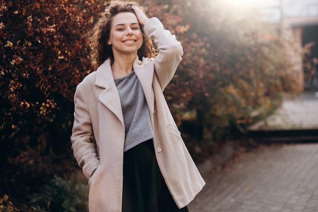 Linda mulher com cabelos cacheados, andando com um casaco de outono Foto gratuita