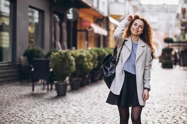 Linda mulher com cabelos cacheados, andando em uma rua de café Foto gratuita