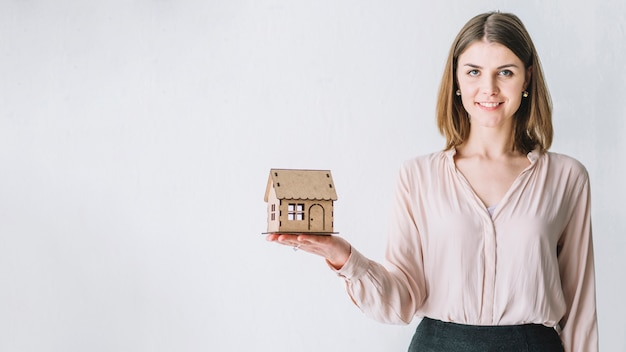 Linda mulher com casa de brinquedo Foto gratuita