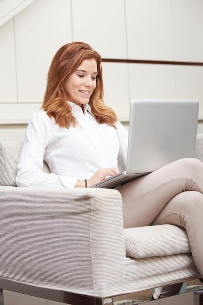 Linda mulher com laptop no sofá Foto Premium