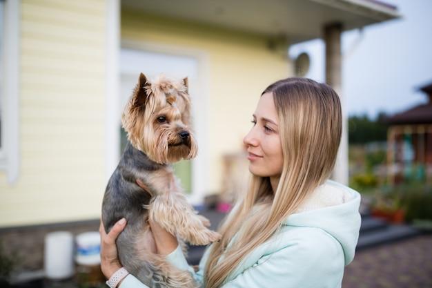 Linda mulher com longos cabelos loiros segurando cachorro yorkshire terrier ao ar livre Foto Premium