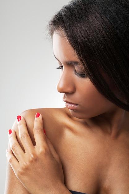 Linda mulher com os ombros nus está tocando seu ombro Foto gratuita