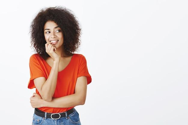 Linda mulher com penteado afro posando no estúdio Foto gratuita
