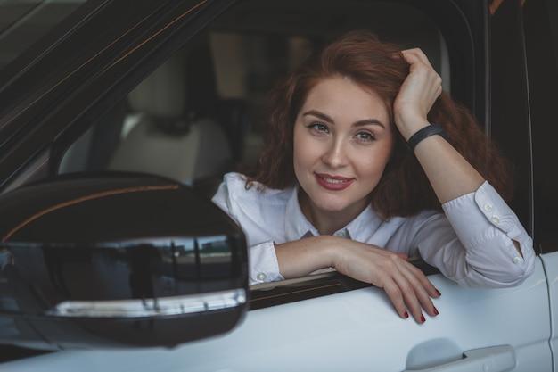 Linda mulher comprando carro novo na concessionária Foto Premium