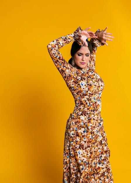 Linda mulher dançando flamenco com fundo laranja Foto gratuita