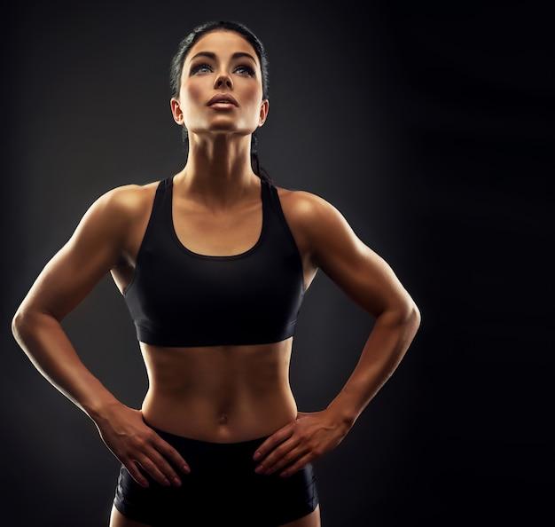 Linda mulher de cabelos negros com corpo bem torneado, vestida com uma roupa esportiva, olhando para cima. mulher esportiva mostrando seu corpo bem treinado fitness, treinamento esportivo e estilo de vida saudável Foto Premium