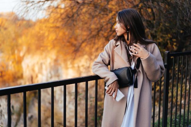 Linda mulher elegante em pé em um parque no outono Foto gratuita