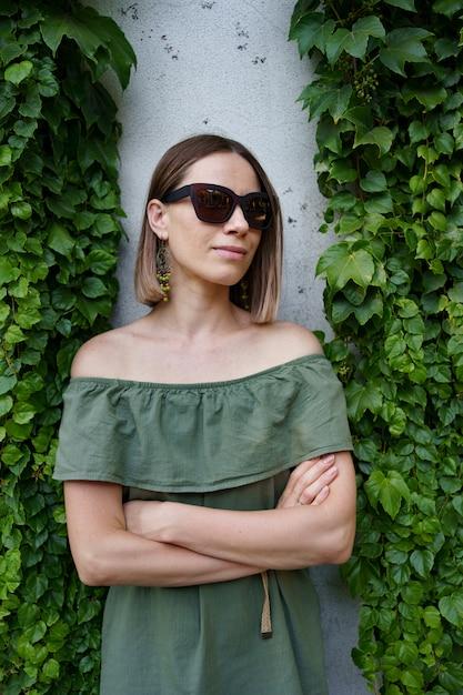 Linda mulher em óculos de sol marrons, posando ao lado de plantas. foto ao ar livre de uma linda jovem em traje verde posando com as mãos cruzadas entre folhas verdes Foto gratuita