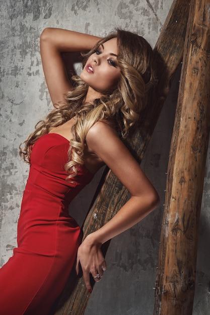 Linda mulher encaracolada no vestido vermelho Foto gratuita