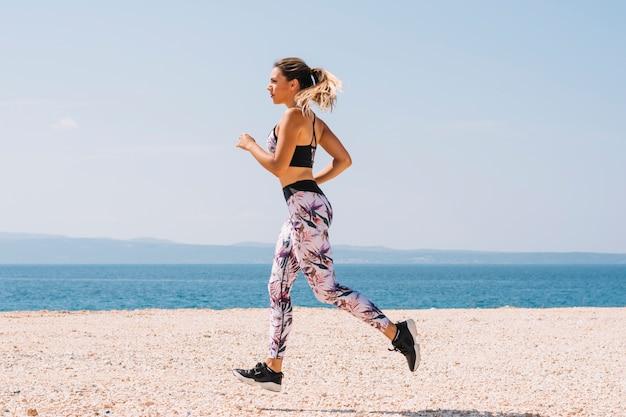 Linda mulher esportiva correndo ao longo da bela praia Foto gratuita