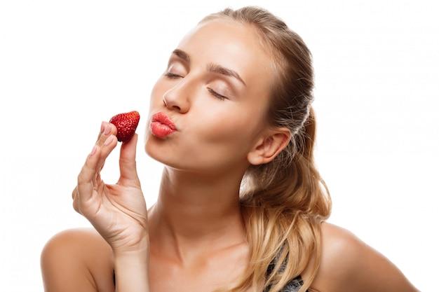 Linda mulher esportiva posando, comendo morango Foto gratuita