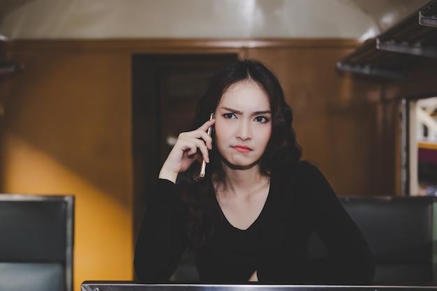Linda mulher está chamando seu namorado ou amigo que eles chegam tão tarde. Foto Premium