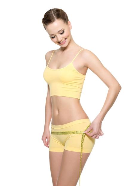 Linda mulher feliz com corpo perfeito, medindo as nádegas com tipo de medição isolado no branco. Foto gratuita