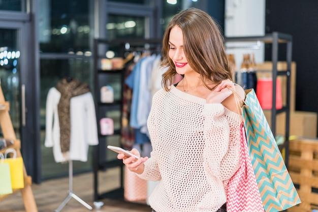 Linda mulher feliz usando telefone celular em um shopping center Foto gratuita