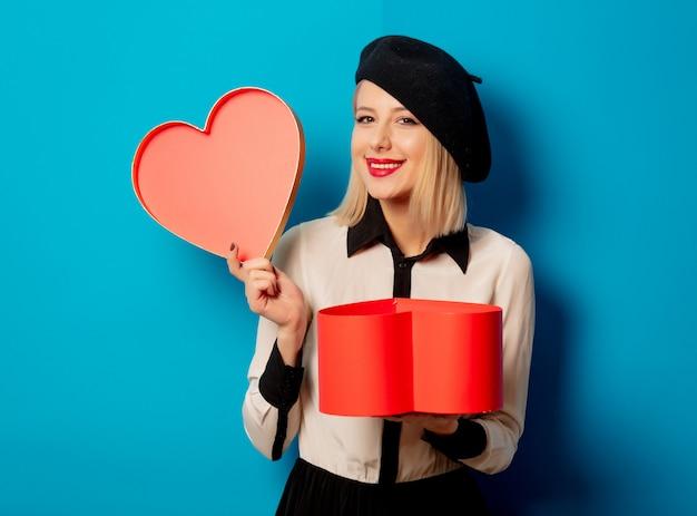 Linda mulher francesa em boina com caixa de presente em forma de coração Foto Premium