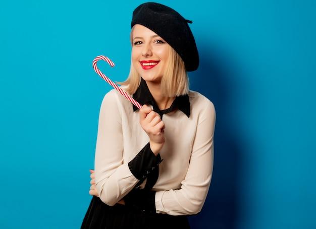 Linda mulher francesa em boina com pirulito doce na parede azul Foto Premium