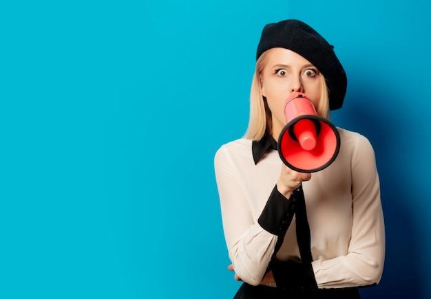 Linda mulher francesa em boina detém alto-falante na parede azul Foto Premium