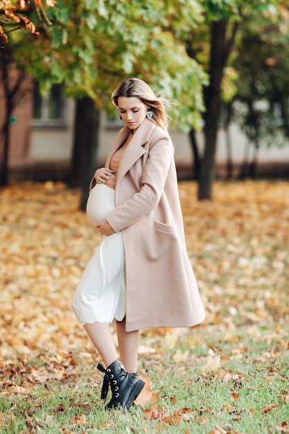 Linda mulher grávida aprecia a gravidez no parque Foto gratuita
