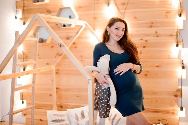 Linda mulher grávida de cabelos compridos com um brinquedo entre as luzes das guirlandas Foto Premium