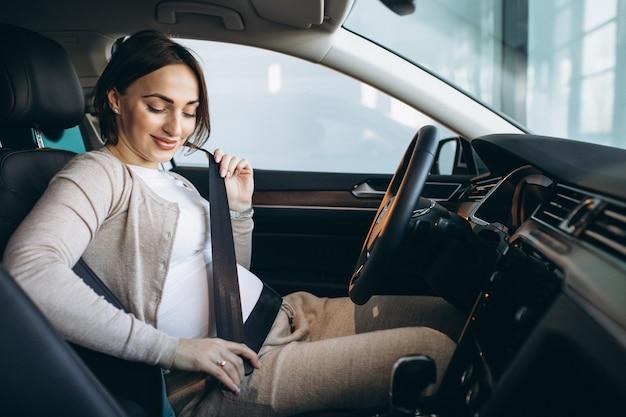 Linda mulher grávida dirigindo carro Foto gratuita